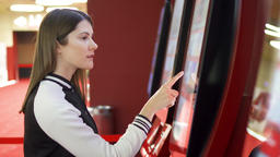 Teenager buying movie ticket from vending machine at cinema. Female make Footage