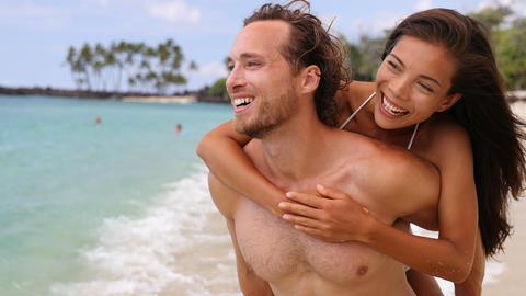 Attractive happy couple laughing having beach fun on tropical beach Footage