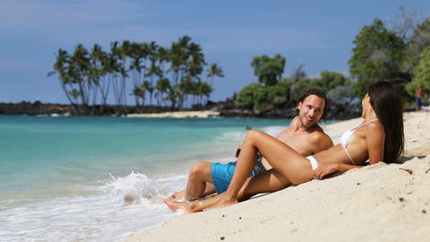 Couple sunbathing on beach vacation relaxation - Happy young adults sunbathing Live Action