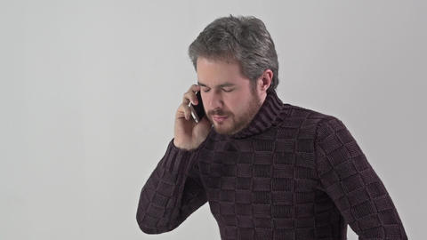 Man in sweater talking on a mobile phone Footage