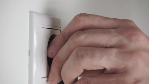 Black plug putting into a wall socket and pulling out rapid Footage