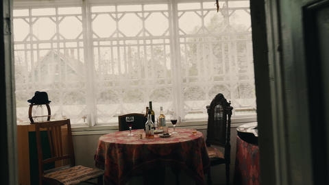 View of table with alcohol drinks on terrace of country house. Summer. Windows Footage