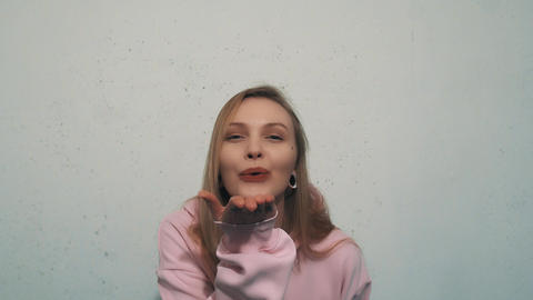Pretty young girl in pink sweatshirt smiling and sent air kiss into camera Footage