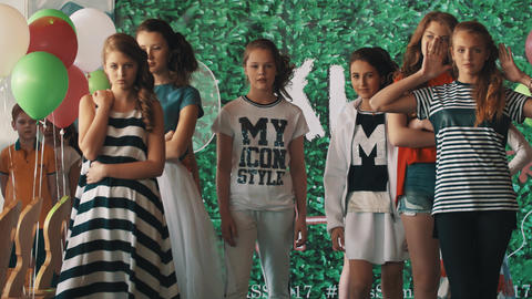 Teenage girls models showing clothes walking on catwalk at kids fashion show Footage