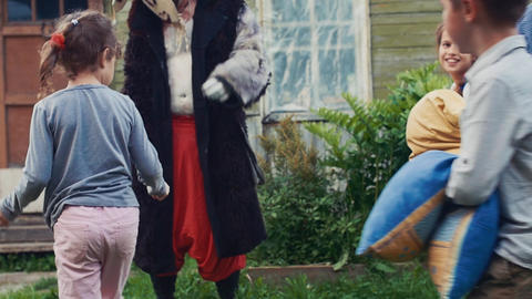Kids fight pillows in yard country house. Countryside. Childhood. Man in costume Live Action