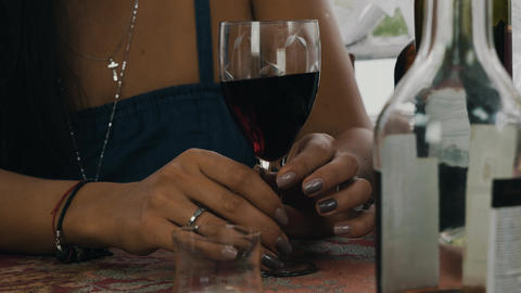 Girl hold in hands glass with red wine at table. Terrace of country house Live Action