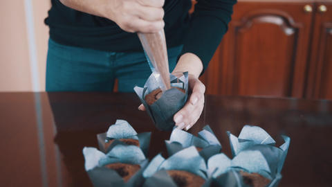 Confectioner female hands squeezes chocolate filling into muffins on table Footage
