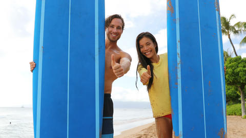 Surfing Cheerful Couple Showing Thumbs Up While Peeking Through Surfboards Footage