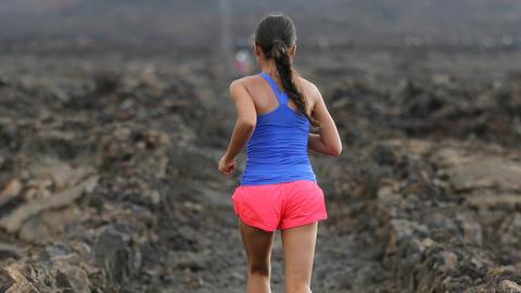 Determined Female Athlete Running On Arid Landscape Live Action