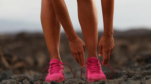 Female Running Athlete Tying Shoelaces On Running Shoes In Arid Landscape Footage
