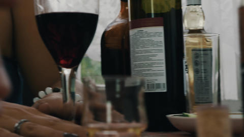 Girl hold in hands glass with red wine at table. Terrace country house. Friends Live Action