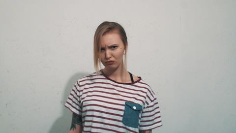 Grumpy blonde girl in striped shirt with tattoos sulks in front of white wall Live Action