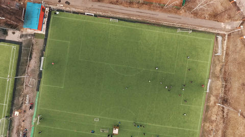 Aerial top view of sportsmen playing football on green grass field on summer day Footage