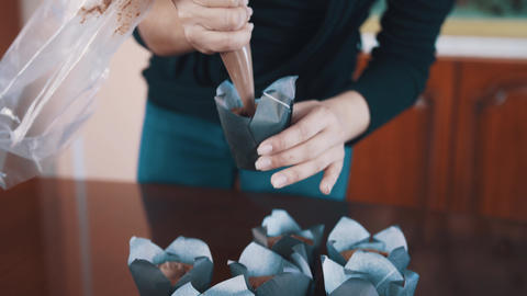 Pastry-cook woman hands squeezes chocolate filling into muffins on table Footage