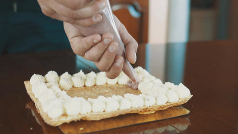 Confectioner male hands squeezes filling creme out sleeve onto cake layer Footage