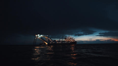Oil producing boat lighted up in night sea waters with last sun beams on horizon Live Action