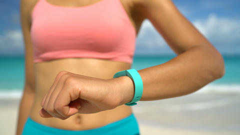 Activity Tracker on Fit Woman Wrist At Beach - Fitness Tracker Wearable Tech Live Action