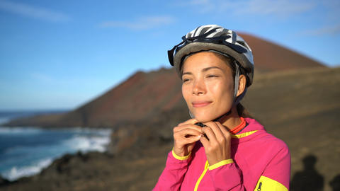 Woman cyclist putting on biking helmet while MTB mountain biking in nature Footage