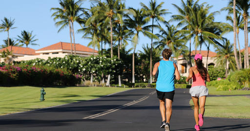 Couple running and jogging in rich beautiful neighborhood on summer day Live Action