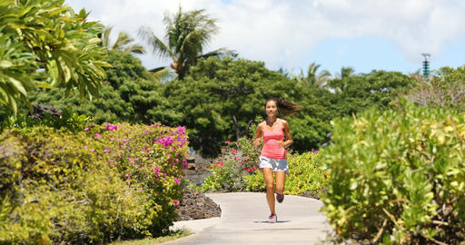 Runner woman running on park path exercising on beautiful summer day Footage