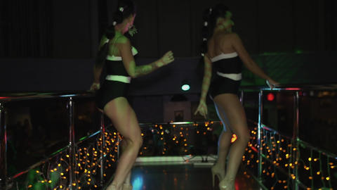 Two go go girls in black bikini suits dance on stand in nightclub. High heels Live Action