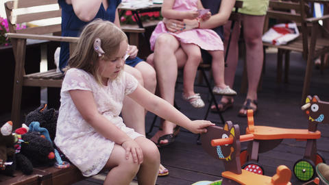 Little girl play with toys at terrace of restaurant. Summer event. People Footage