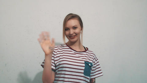 Pretty girl in striped shirt smiling and waving hand on... Stock Video Footage