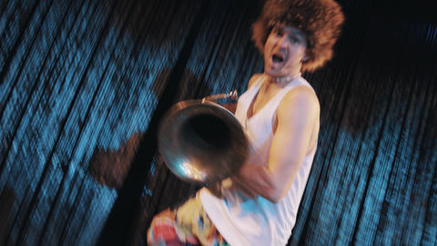 Crazy tattooed man in tank top and big fur hat perform with brass tube on scene Footage