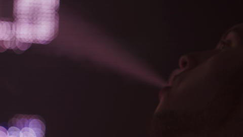 Boy exhale steam from electronic cigarette in nightclub. Spotlight. Vaper. Steam Live Action