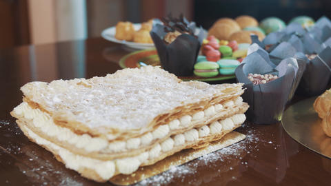 Sugar powder strew on layered cake on table with lots of dessert products Footage