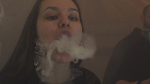 Girl exhale steam from electronic cigarette. Vaper. Subculture. Smoker Live Action