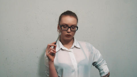 Thoughtful woman in white shirt, with ear flesh tunnels bites on pen, thinking Live Action