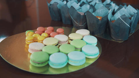 Multicolored macaroons and mini cakes on kitchen table Footage