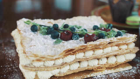 Female hands decorates layered cake covered in sugar powder with mint leaves Footage
