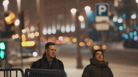 Two young guys walking down night city street in snowfall Footage