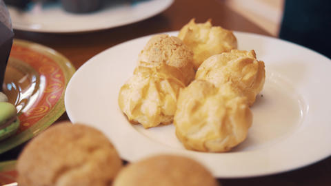 Sugar powder pour on profiteroles on table with lots of baking products Footage