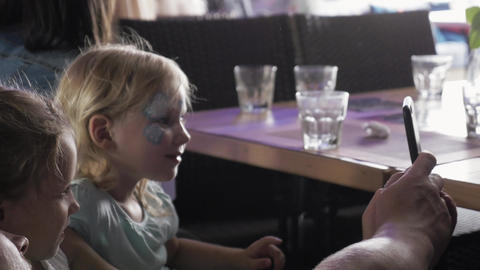 Two teen girls take selfie with father. Painted faces. Children event. Celebrate Footage