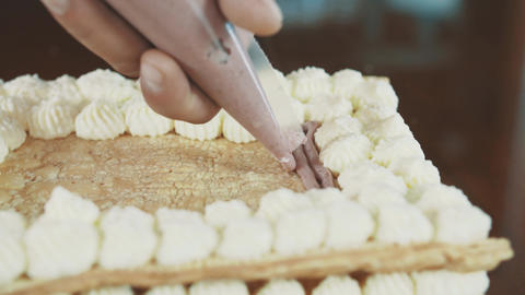 Confectioner man hands squeezes filling creme out sleeve onto cake layer Footage