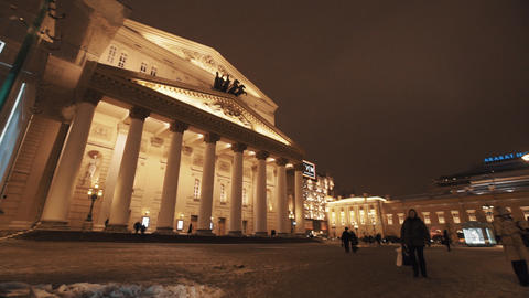 People passing by in front of theater building on winter night Footage
