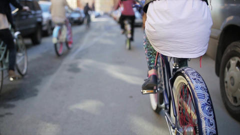 Back side of girl cycling among other cycling people in summer day. Slow motion Live Action