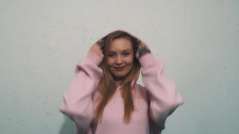 Cute blonde girl smiling puts on sweatshirt hood and snuggle on white wall Footage