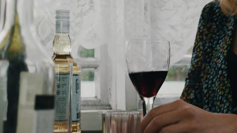 Blonde girl sing at table drink red wine on terrace of country house. Resting Footage