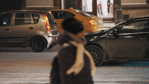 Car traffic at winter night city street during snowfall Footage