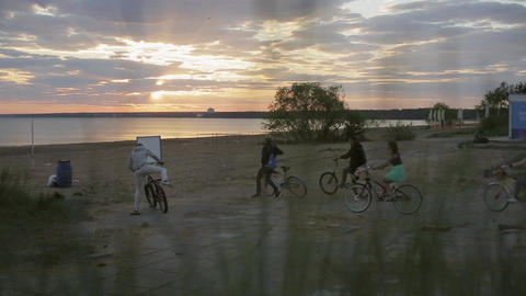 Group of people arrive on a beach, leave their bicycles, run to water in sunset Footage