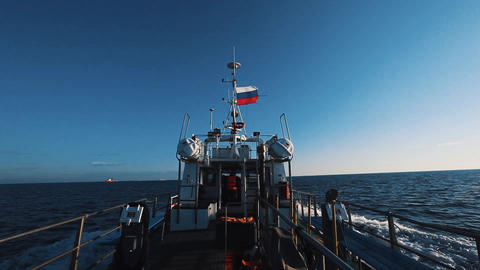 Motor boat with russian flag fast going over sea water under clear sky Footage