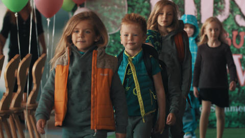 Line of little kids walking on catwalk showing winter clothes at fashion show Footage