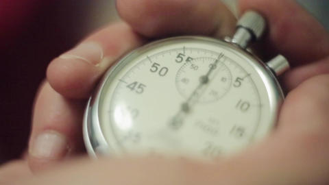 Man hands push button of old round stopwatch. Close up Footage