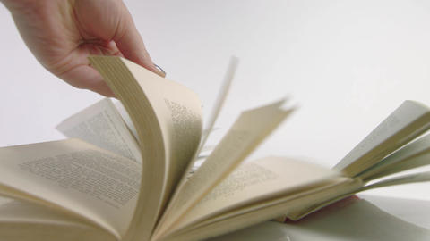 Hand flicking through books on white background Live Action