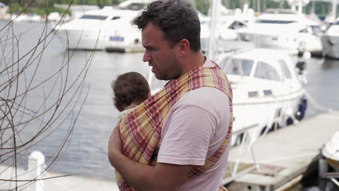 Father hold in sling little baby walking at seafront. Event. Summer sunny day Footage
