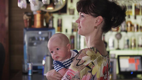Mother with cute baby boy in restaurant on celebration event. Happiness. Bar Footage